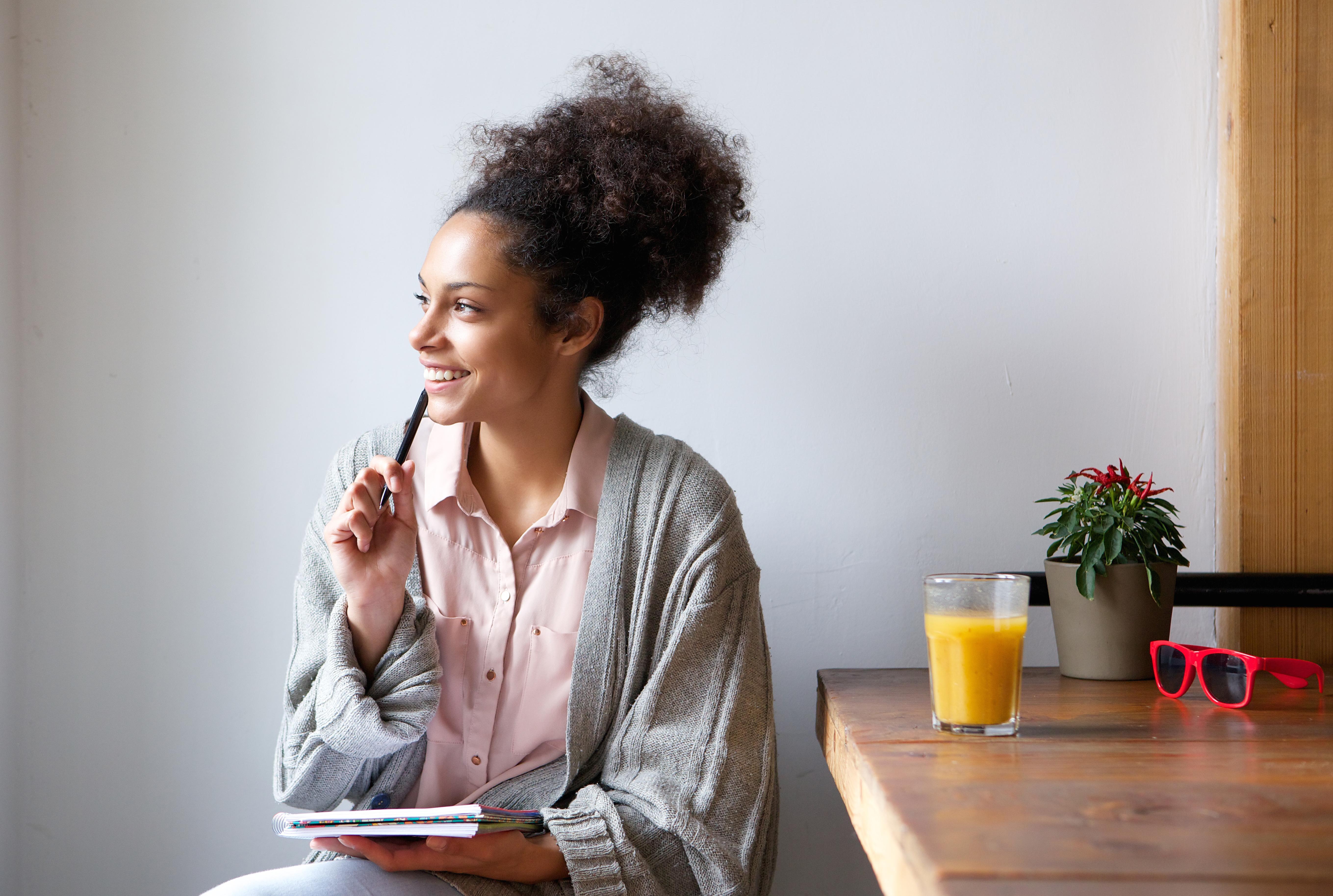 imagem_horizontal_1_construir_disciplina_financeira mulher bonita pensando com um caderno na mão olhando para o horizonte