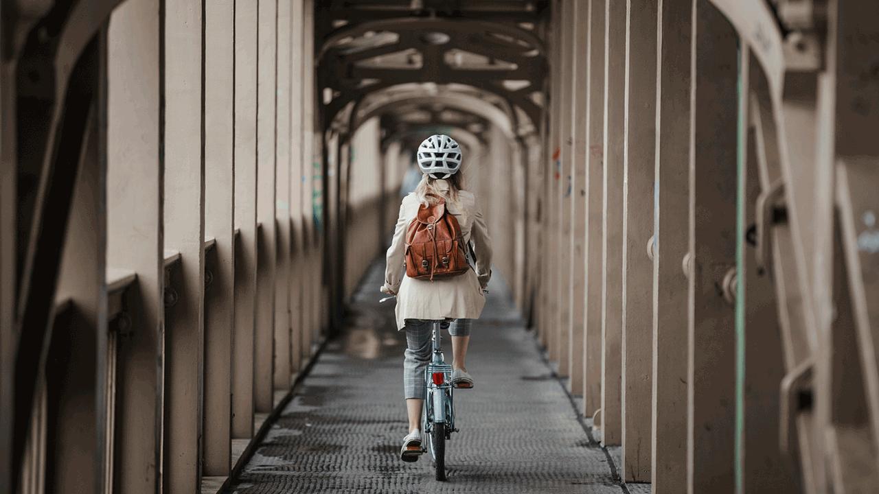 Bicicleta. Mulher andando de bicicleta. Meios de transporte mais baratos.
