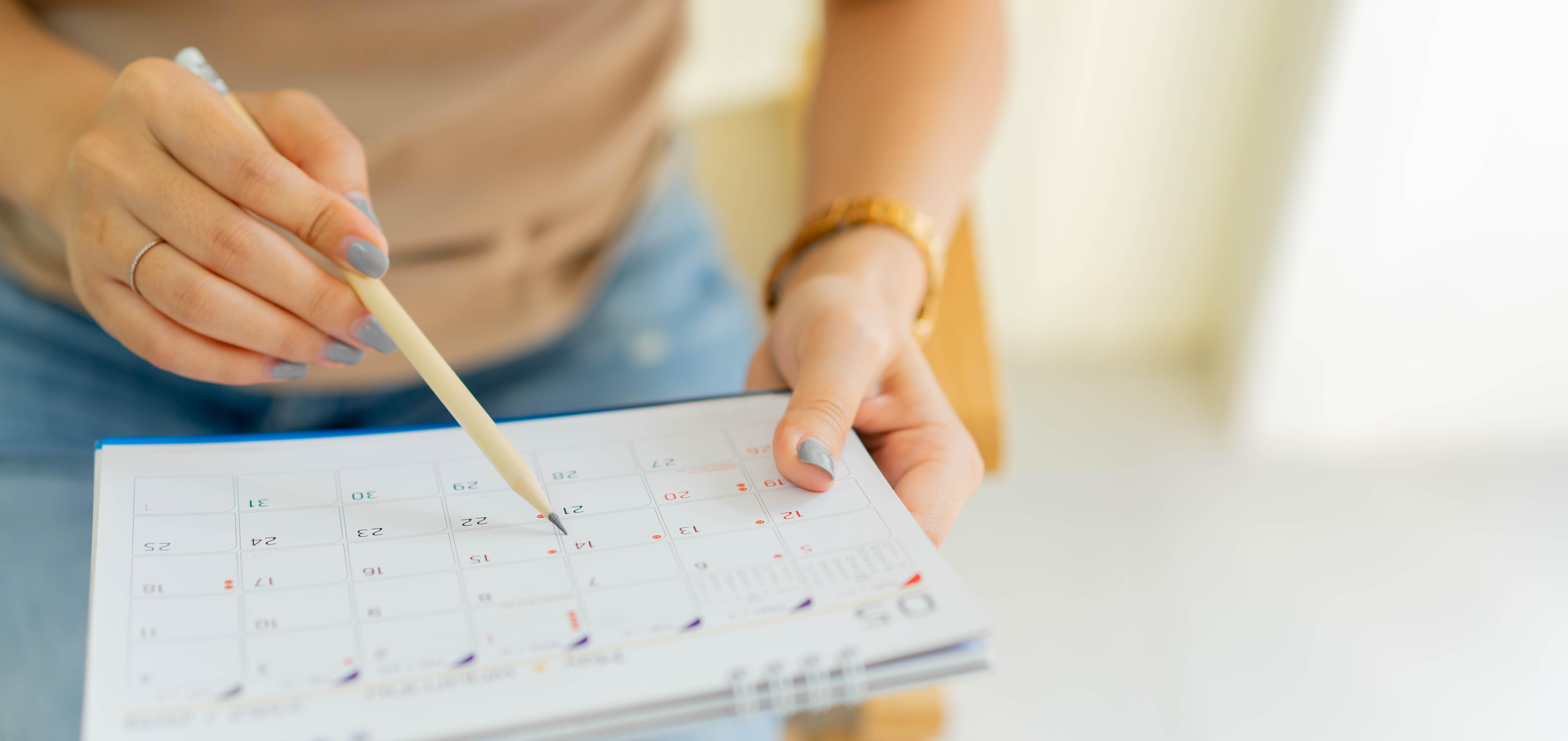 Matéria MBD - Dicas para cartão de crédito - Mão de mulher usando caneta para escrever no calendário - palavras-chave:Calendário, Agenda pessoal, Organização, Controle