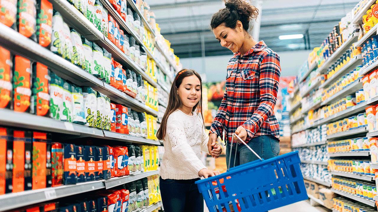 educação financeira para crianças de diferentes idades. mãe e filha fazendo compras no supermercado.