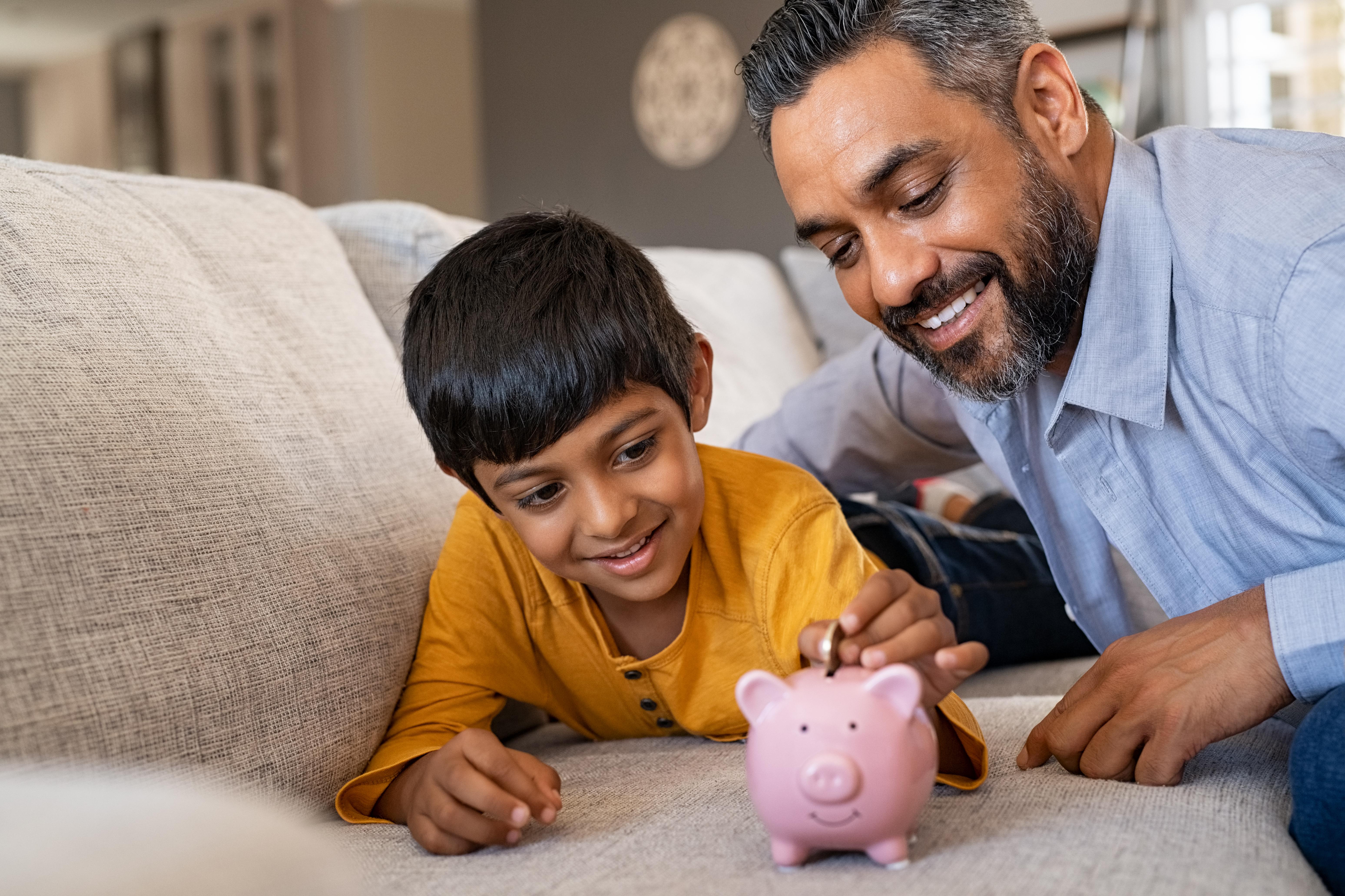 Matéria MBD - Dia dos Pais - Garoto latino economizando dinheiro em cofrinho -palavras-chaves:República da África do Sul, Criança, Poupança, Moeda Corrente, Finanças