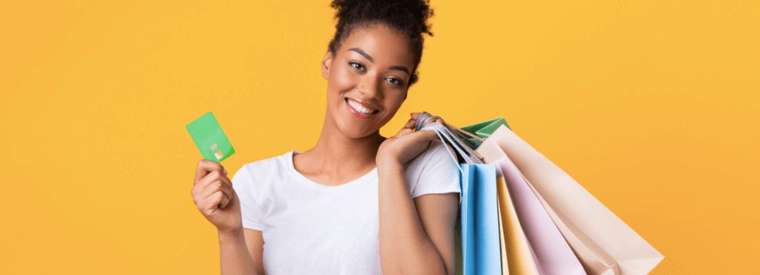Matéria de Cashback - MBeD - Mulher negra sorridente segurando cartão de crédito e sacolas de compras