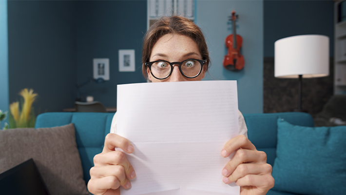 eficiência financeira no seu holerite mulher olhando para papel com surpresa