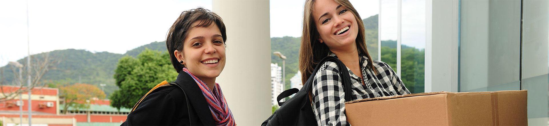 duas mulheres jovens brancas sorridentes com caixas e malas de mudança