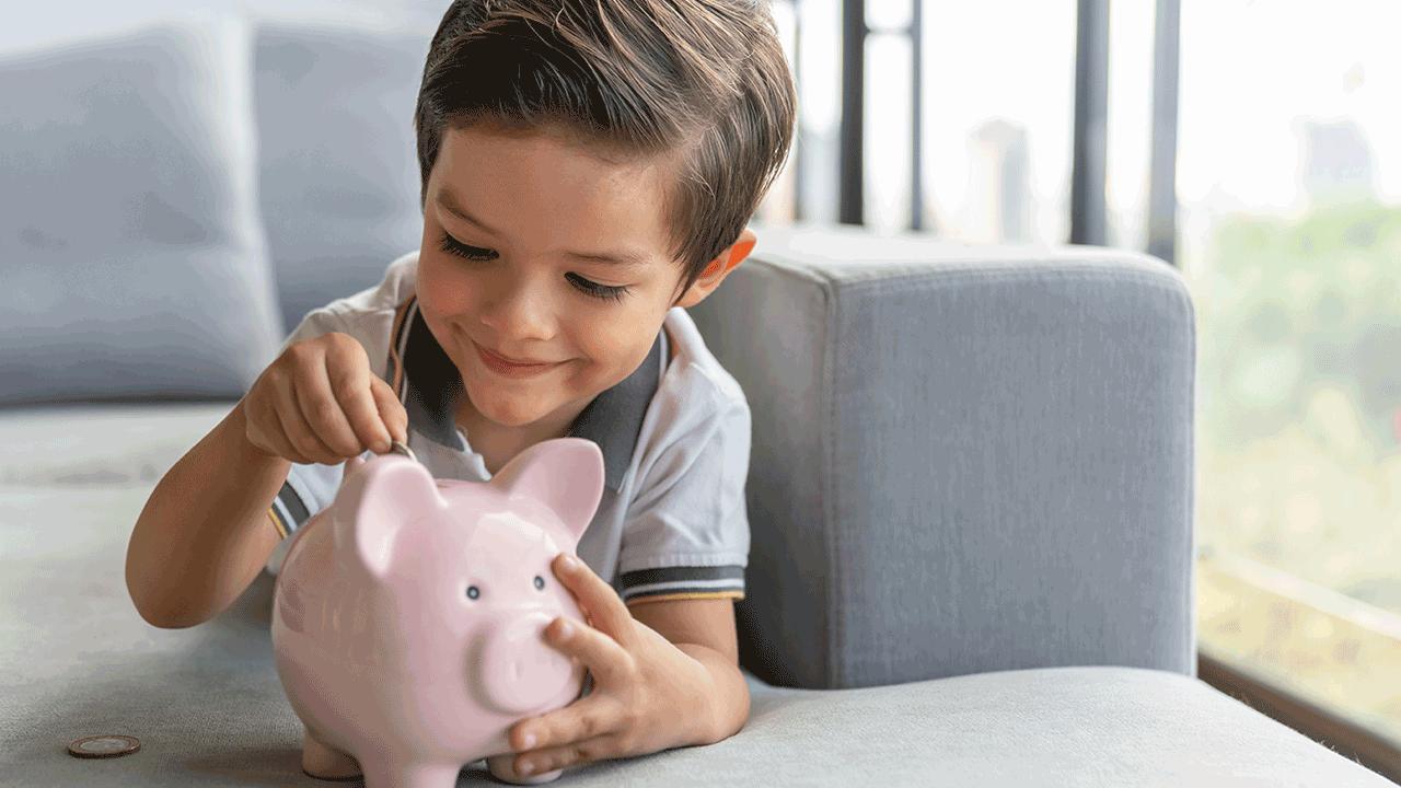 educação financeira para crianças de diferentes idades. menino colocando moeda em cofrinho.