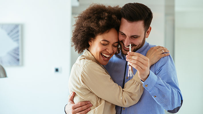 MBeD Post Casal inter-racial feliz segurando chave casa própria 710x400