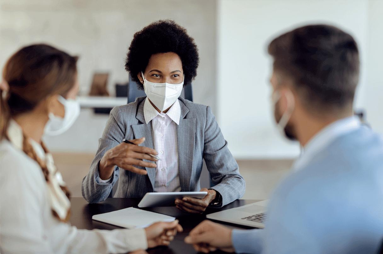 Matéria MBD - Cheque Especial - Consultor financeiro afro-americana conversando com um casal, usando máscara facial protetora.