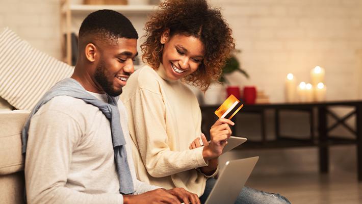 Casal feliz com um cartão de crédito consignado na mão